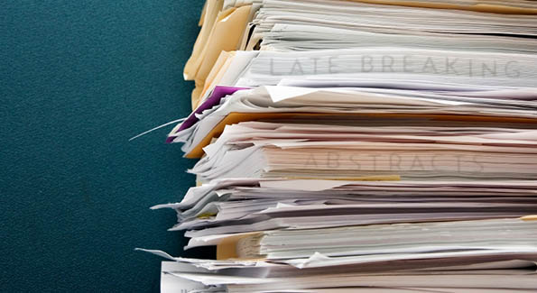 Stack of papers and file folders with 'Late-Breaking Abstracts' hidden in the pages.